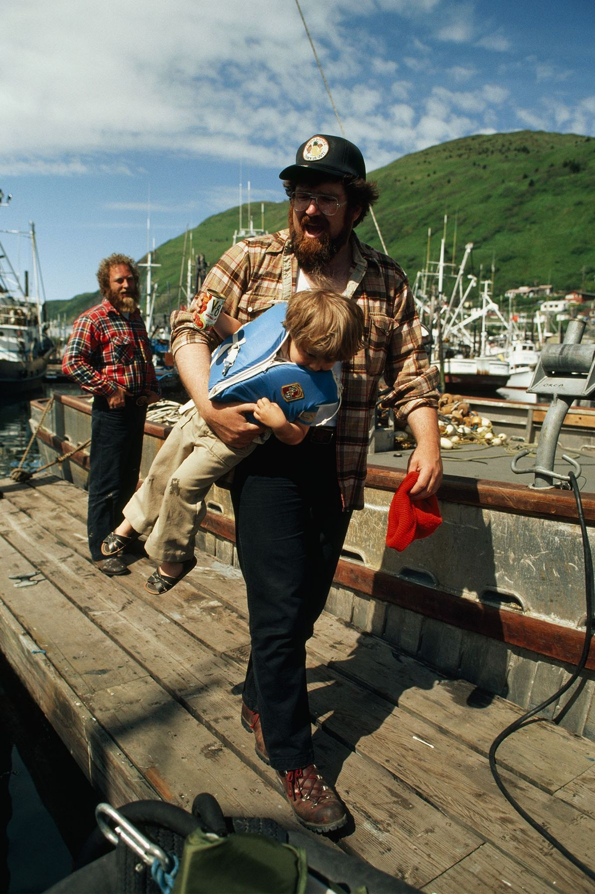 A man carries his son on a pier in Kodiak Island, Alaska, in the 1970s.