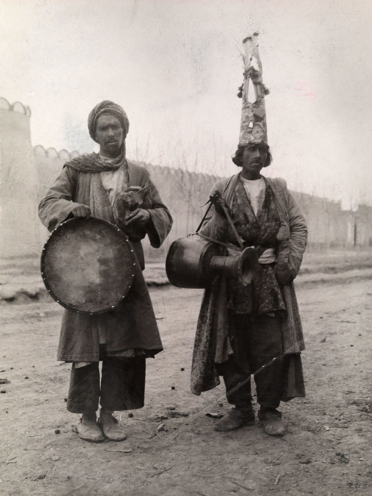 Two Persian fakirs wear outfits that show their time spent on the road, traveling to different ...