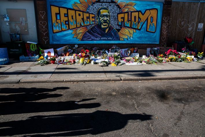 A mural of Floyd looks upon the flowers and candles left by mourning Minnesotans.