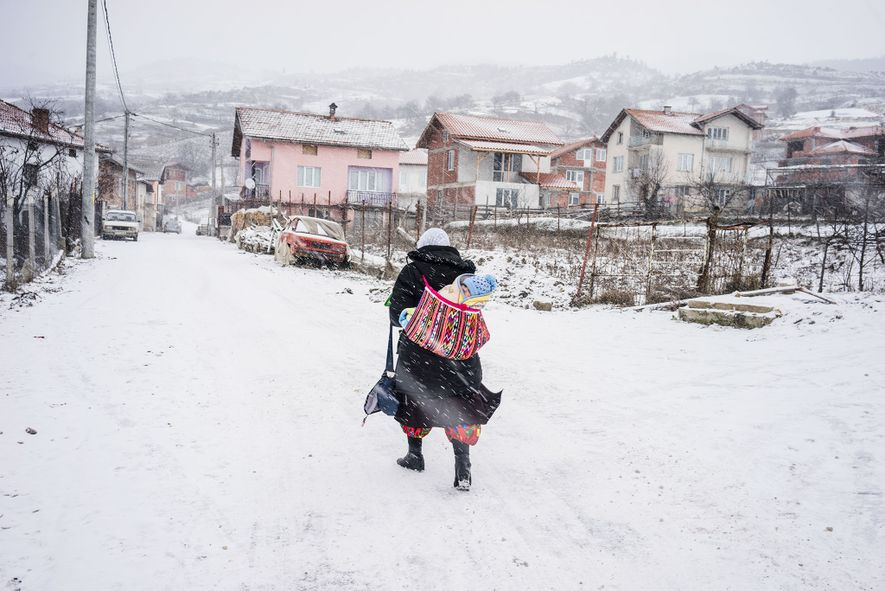 In Ribnovo, a Pomak woman carries her baby in the snow.