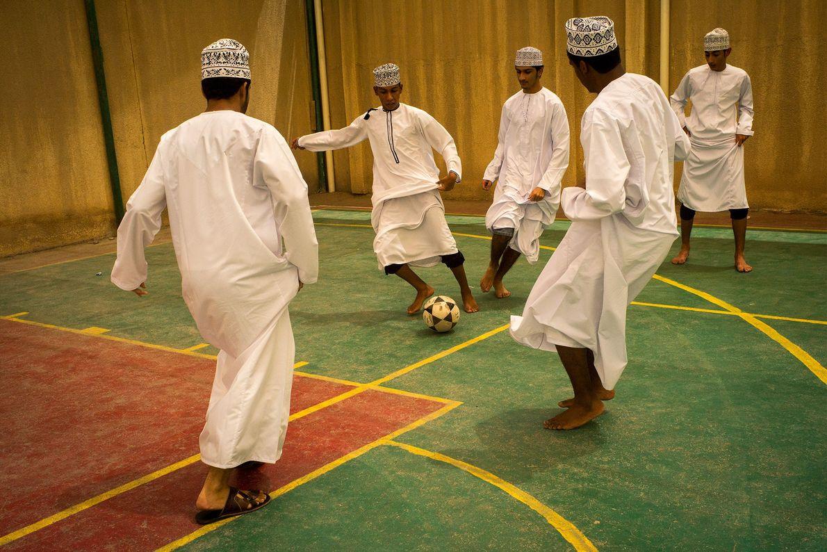 Boys practice football indoors while wearing traditional dishdasha in Al Seeb, Oman. Some indoor football players ...