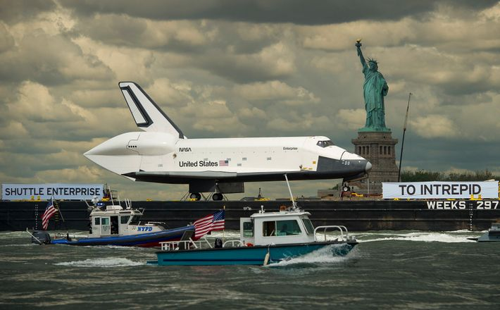 Perched atop a barge, the space shuttle Enterprise passes the Statue of Liberty on June 6, ...