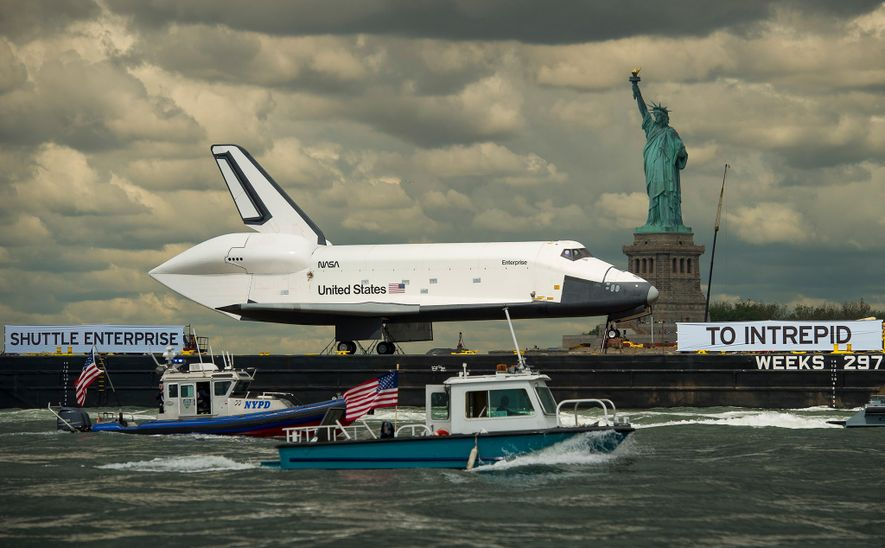 Perched atop a barge, the space shuttle Enterprise passes the Statue of Liberty on June 6, 2012, on its way to New York City's Intrepid Sea, Air & Space Museum, where the shuttle is now permanently displayed.