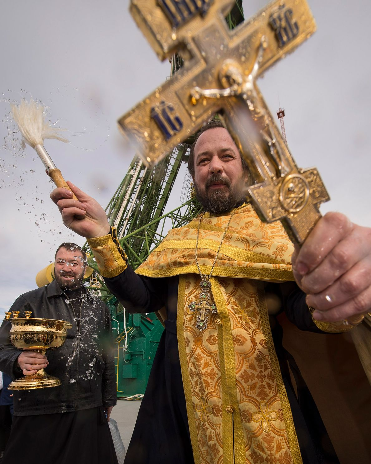 An Orthodox priest blesses members of the media next to the Soyuz rocket at the Baikonur ...