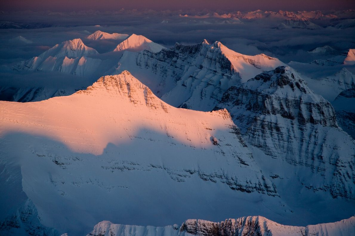 Picture of sunrise turning snowy mountains pink in Montana's Glacier National Park