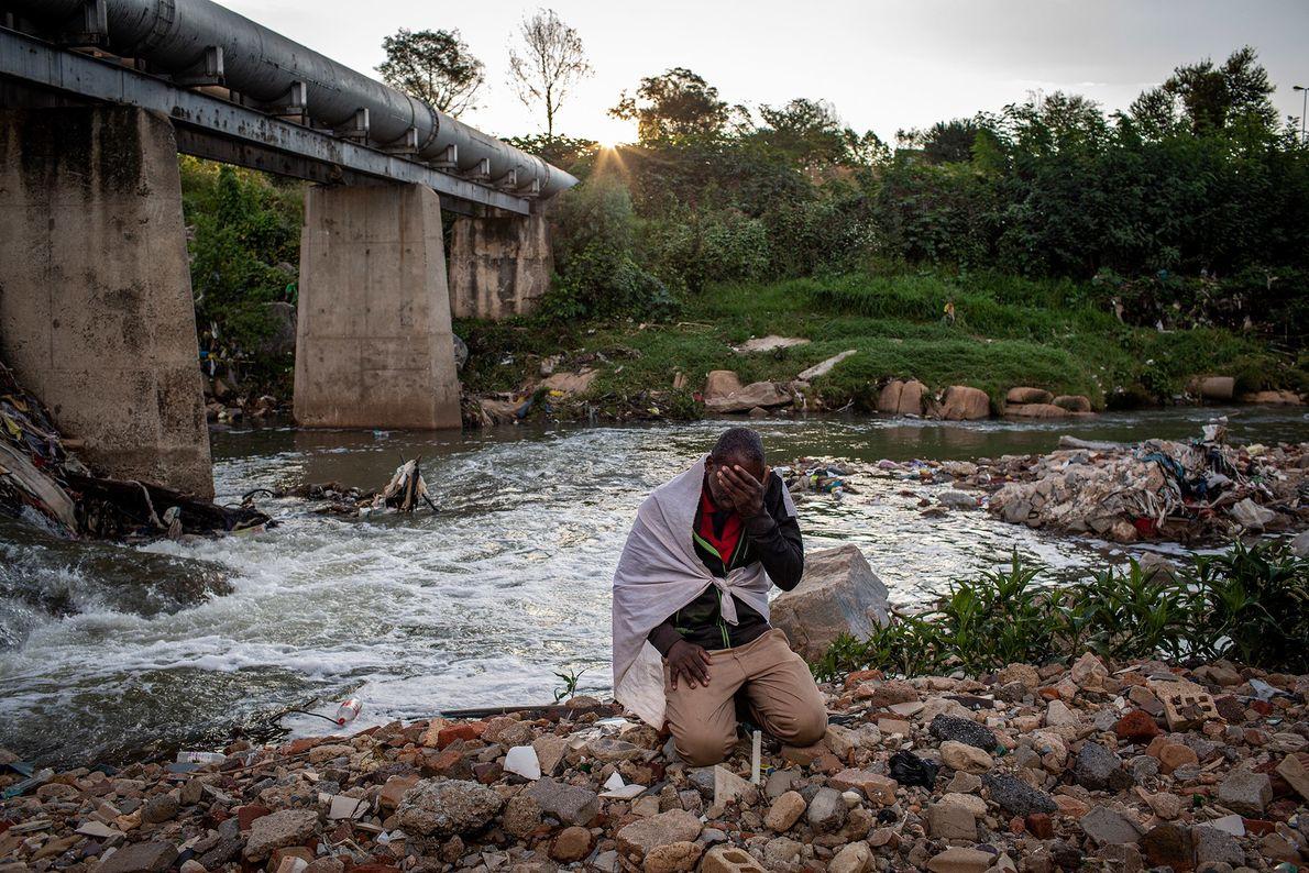 Listen Dube, 37, kneels in prayer on the banks of the Jukskei River in Alexandra Township, ...