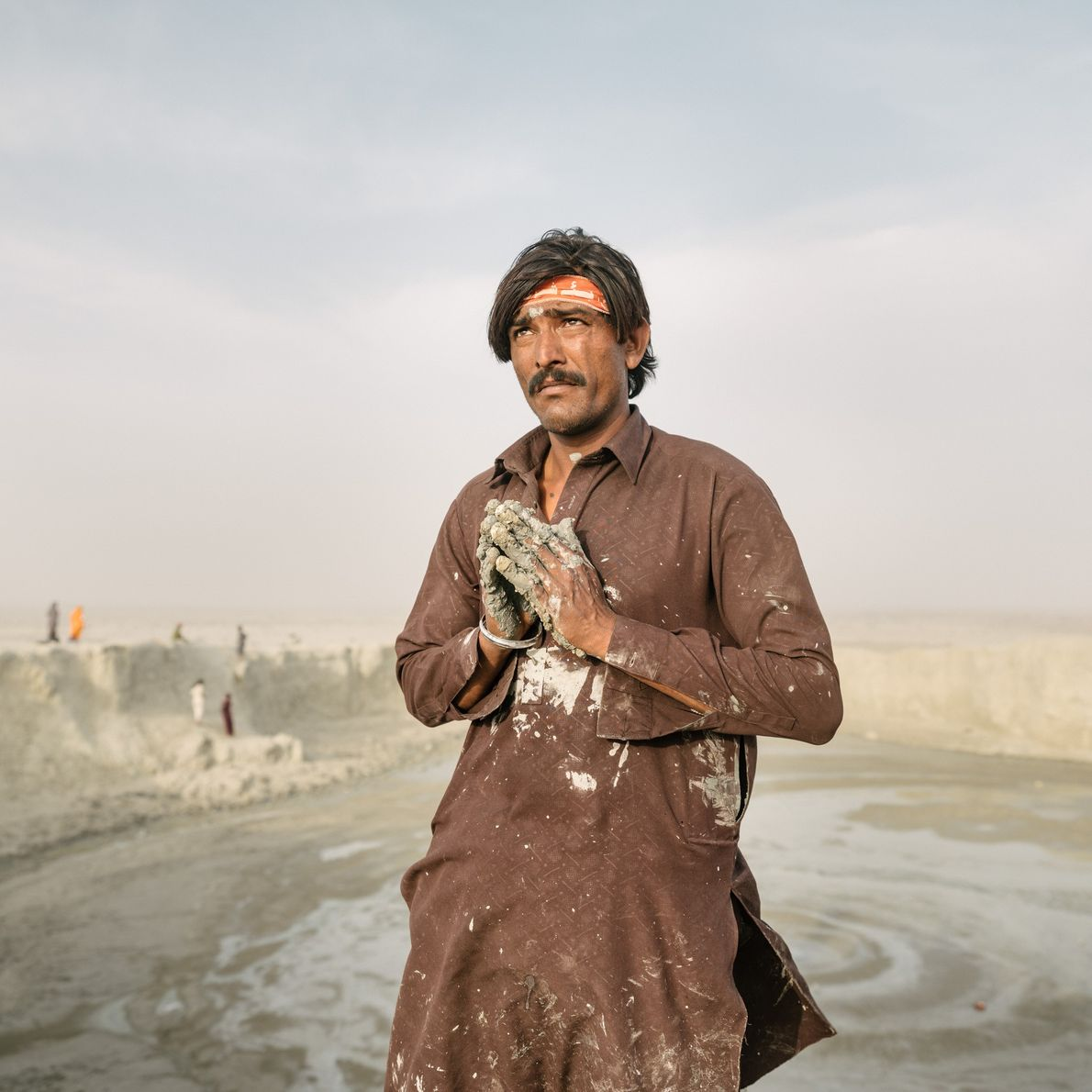 Hands caked in mud, a pilgrim circumnavigates the Chandragup mud volcano.