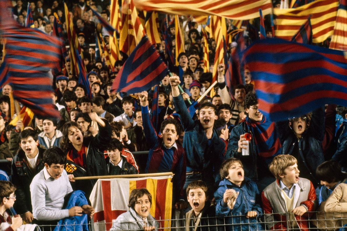 Football fans cheer for Barcelona's team in a game against Madrid in the Catalonia region of ...
