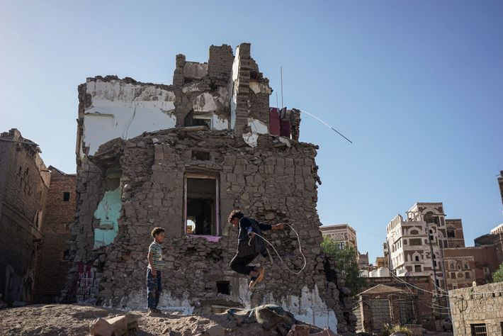 Children play in the aftermath of a bombardment on their neighborhood in the Yemeni capital of ...