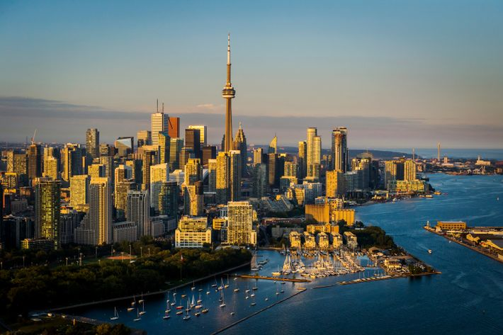 Panoramic view of the Toronto waterfront and Lake Ontario at dusk.