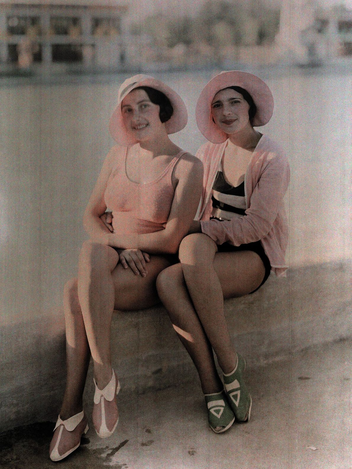 Girls in matching bathing suits and caps sit on a concrete ledge in Bucharest, Romania.