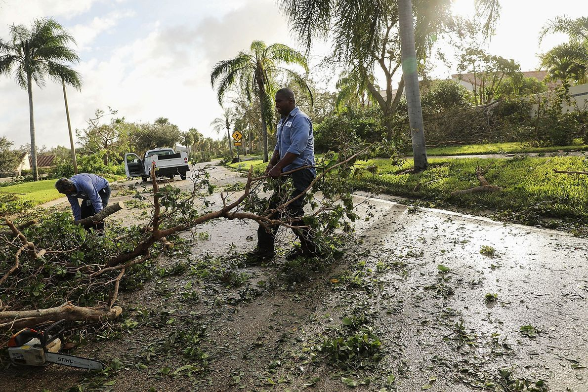 Men clear debris from a roadway the morning after Hurricane Irma swept through the area on ...