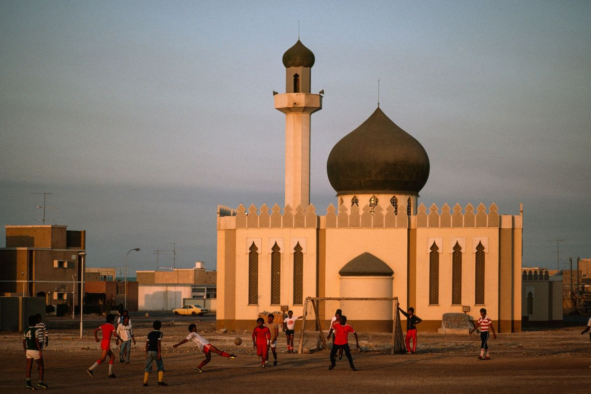 Boys play football in front of a newly built mosque in Isa Town, Bahrain, in 1979.