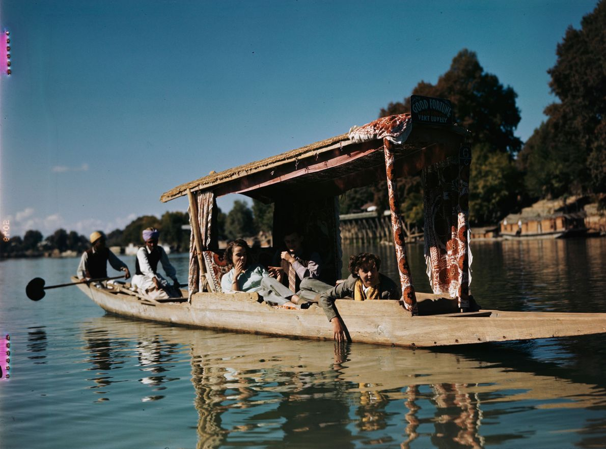 Sightseeers under canopy float down the river soaking up the sights of India.