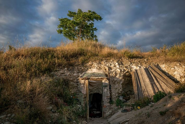 The front door of a cave protrudes slightly from a rocky wall in Sacromonte. Many of ...