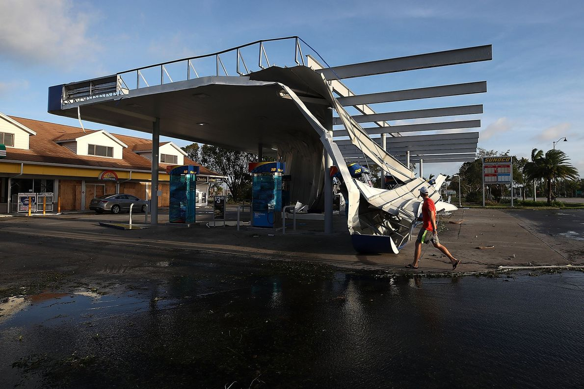 A man walks past the damaged roof of a gas station in Bonita Springs, Florida on ...
