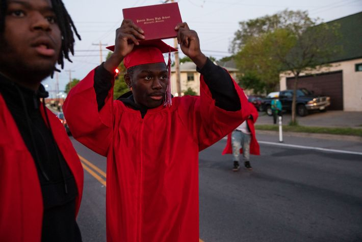 Datelle Straub lifts his diploma as police approach protestors. He and his friends Avery Lewis, and ...