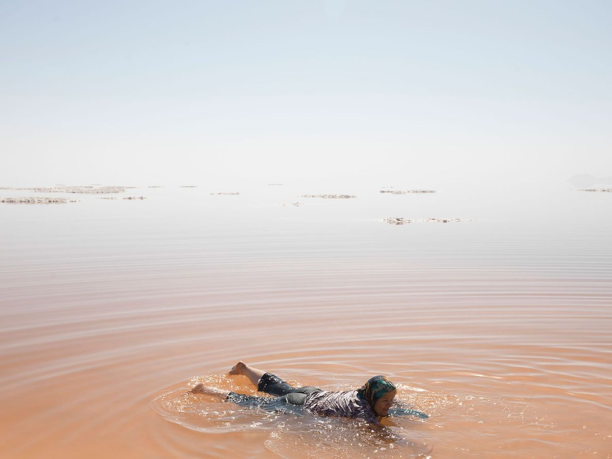 A girl splashes in Lake Urmia, Iran. Summertime bathers wade into waters colored red by salt-loving ...