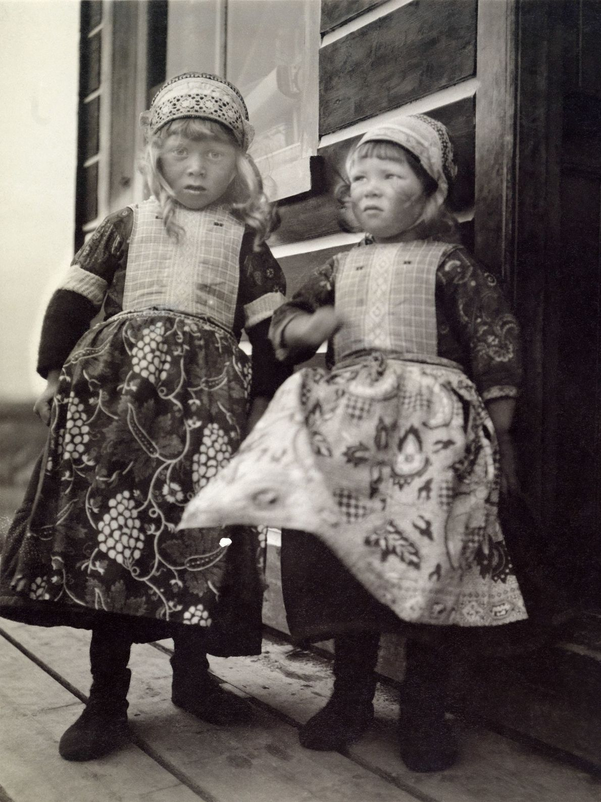Two young girls in traditional Dutch outfits and caps stand outside in Marken Island, Holland.