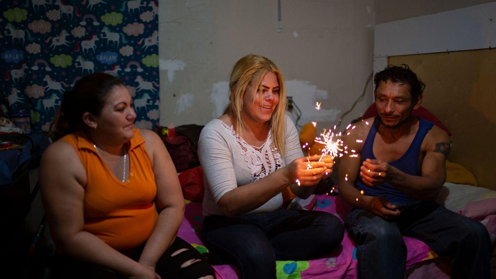 Kataleya Nativi Baca, a transgender Honduran seeking asylum in the U.S., holds a sparkler on December ...