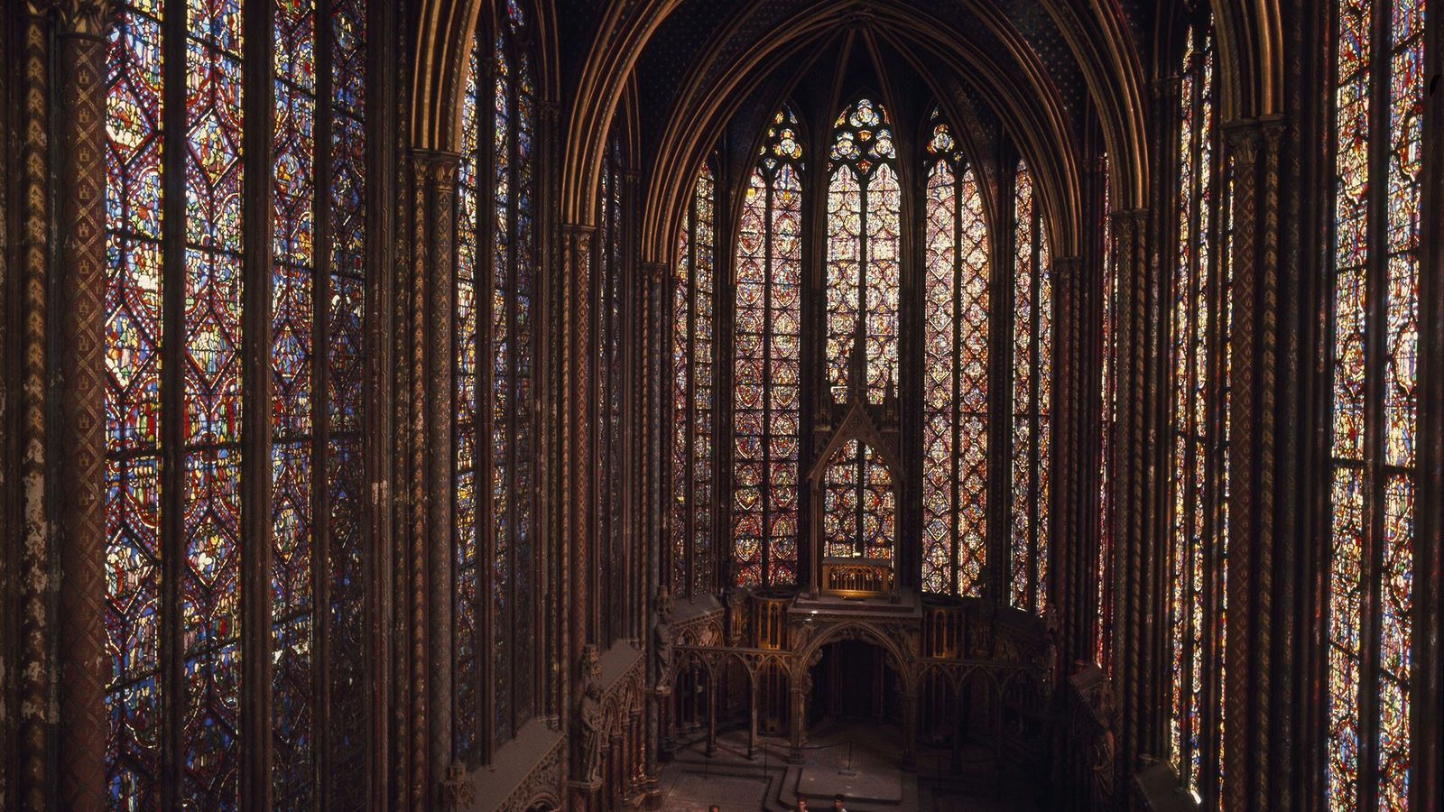 Stained glass hangs like tapestry in the upper chapel of the Sainte Chapelle. Figures of apostles ...