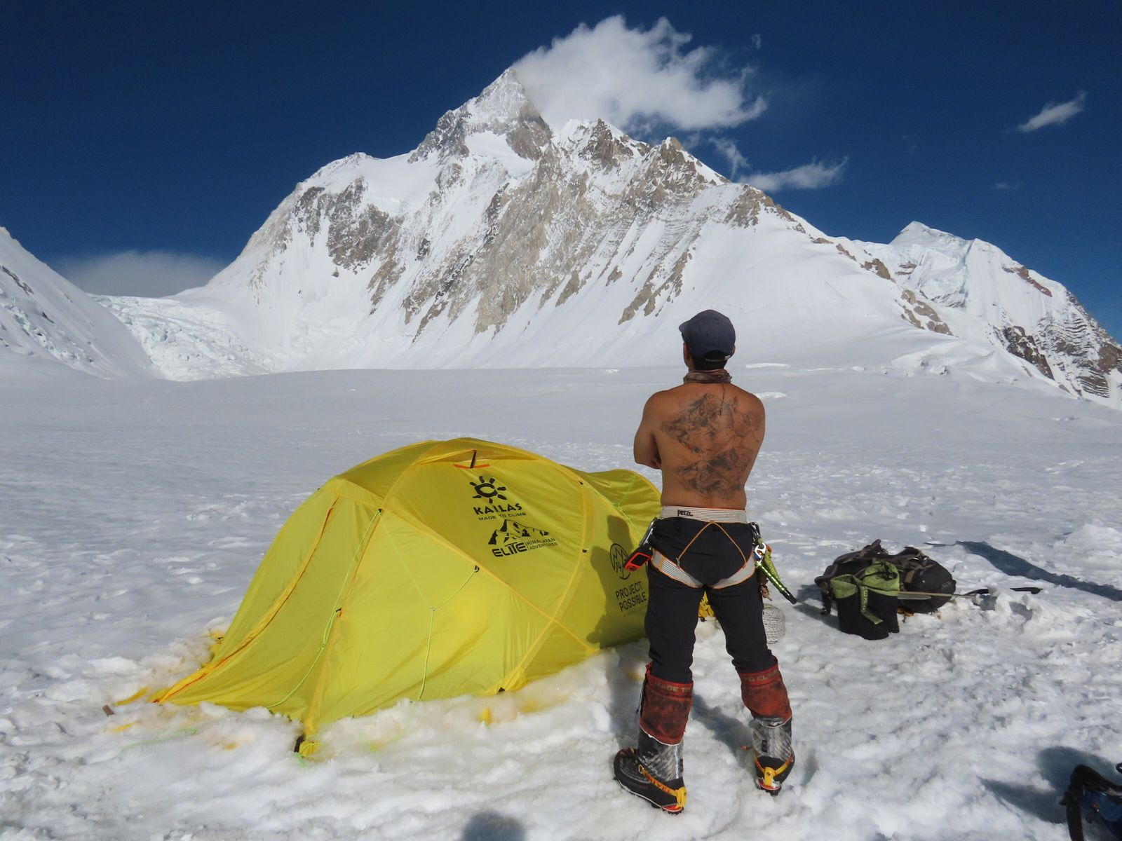 Displaying his DNA-infused tattoo, Nims Purja surveys Kashmir's Gasherbrum massif from his basecamp.
