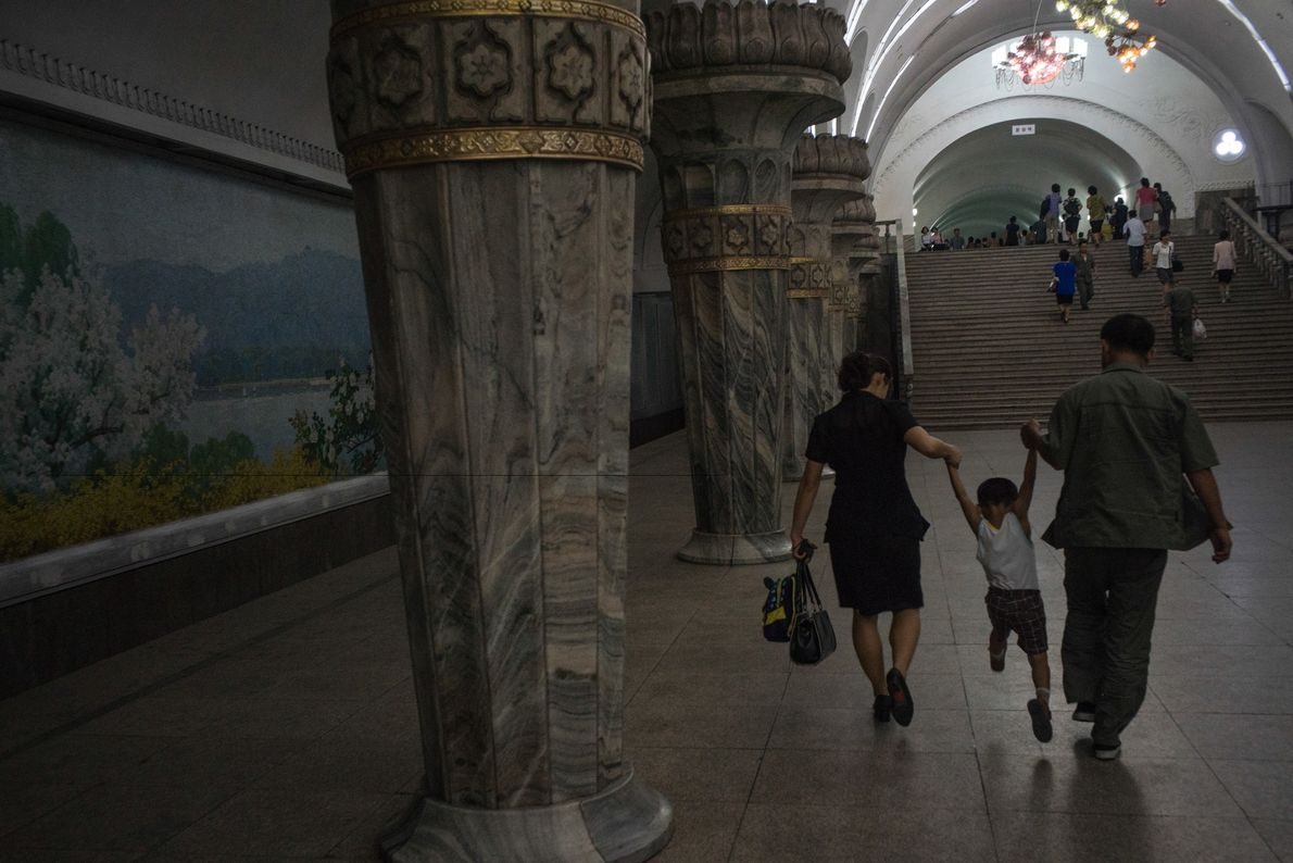 Commuters play with their child in a Pyongyang subway station after disembarking from a train.