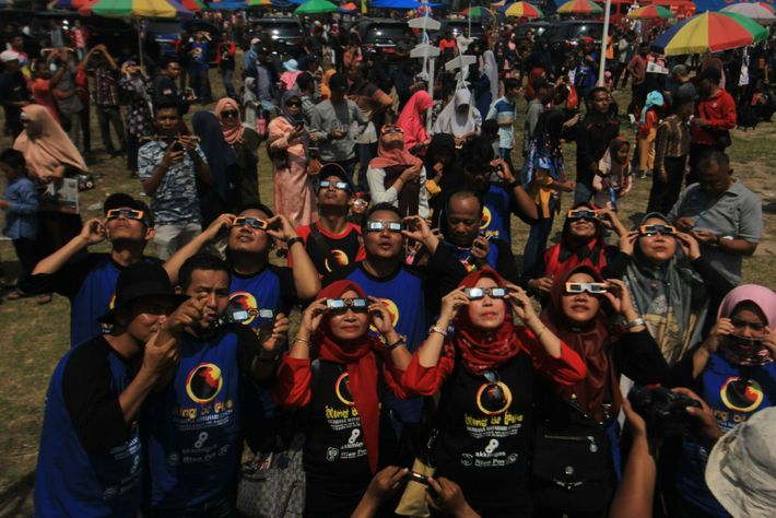 Observers in Siak, Riau, Indonesia watch the 2019 total eclipse through specially filtered glasses. Eclipses take on ...