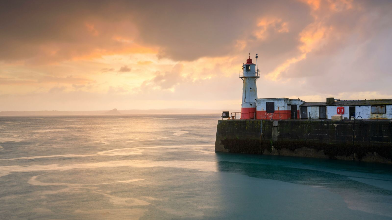 A modern view of Newlyn lighthouse, with St Michael's Mount visible through the haze in the ...