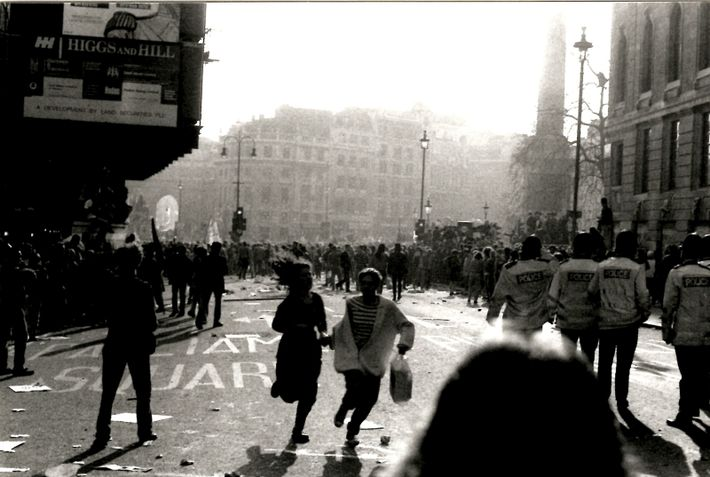 Pedestrians run for cover during the violent poll tax riots in Trafalgar Square, London, March 1990. ...