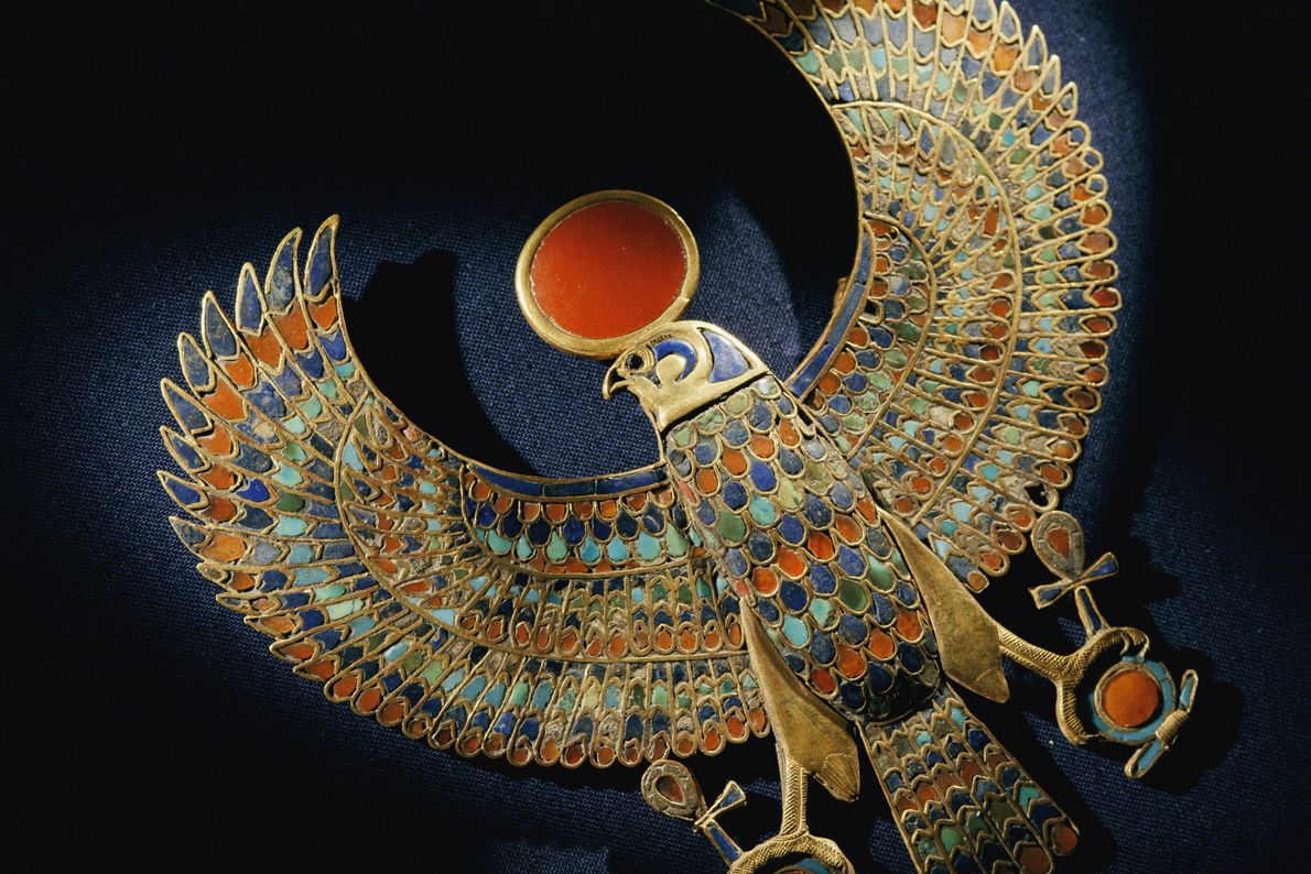 Gold pendant of hawk with semiprecious stones and coloured glass.