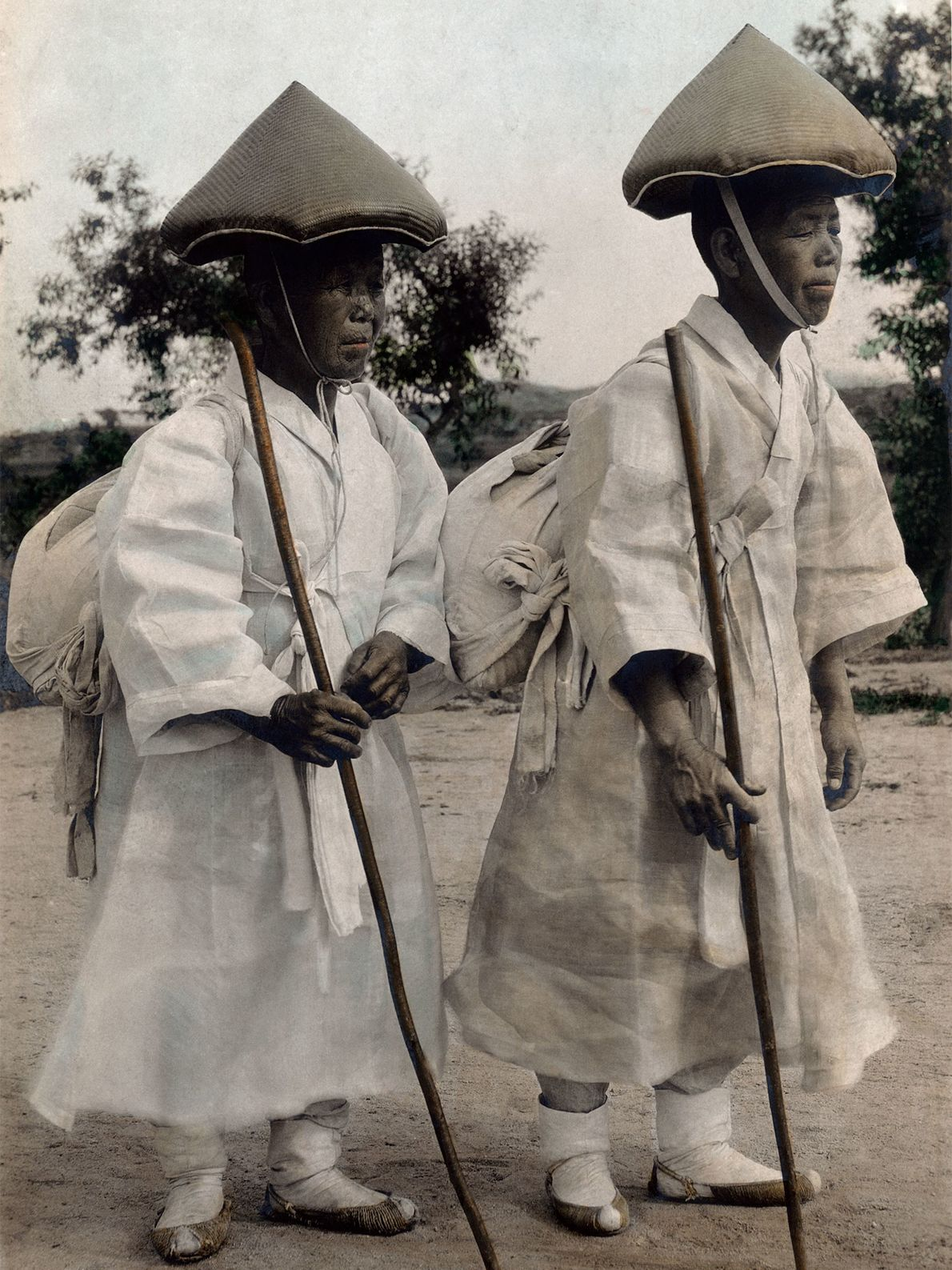 Buddhist nuns wearing songnaks walk with staves near Seoul, Korea, in the early 1900s. The conical ...