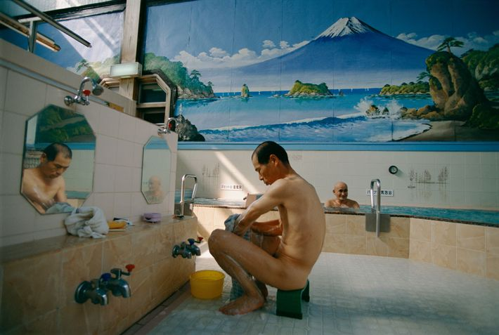 A man bathes in a Tokyo bathhouse decorated with a mural of Mount Fuji.
