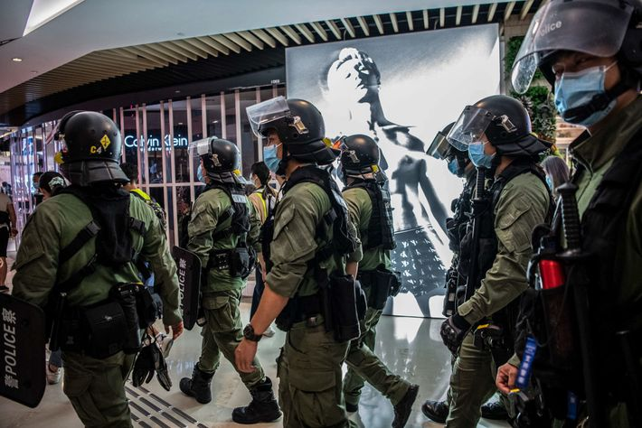 Police walk through the YoHo Mall in Yuen Long, Hong Kong on July 21, the anniversary ...