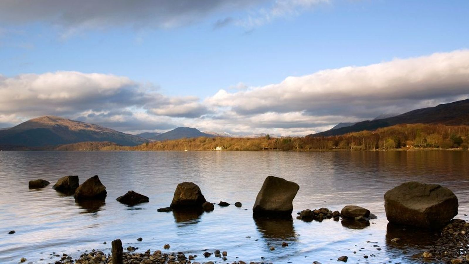 Rocks lead out to Milarrochy Bay in Loch Lomond, the largest lake in Great Britain.