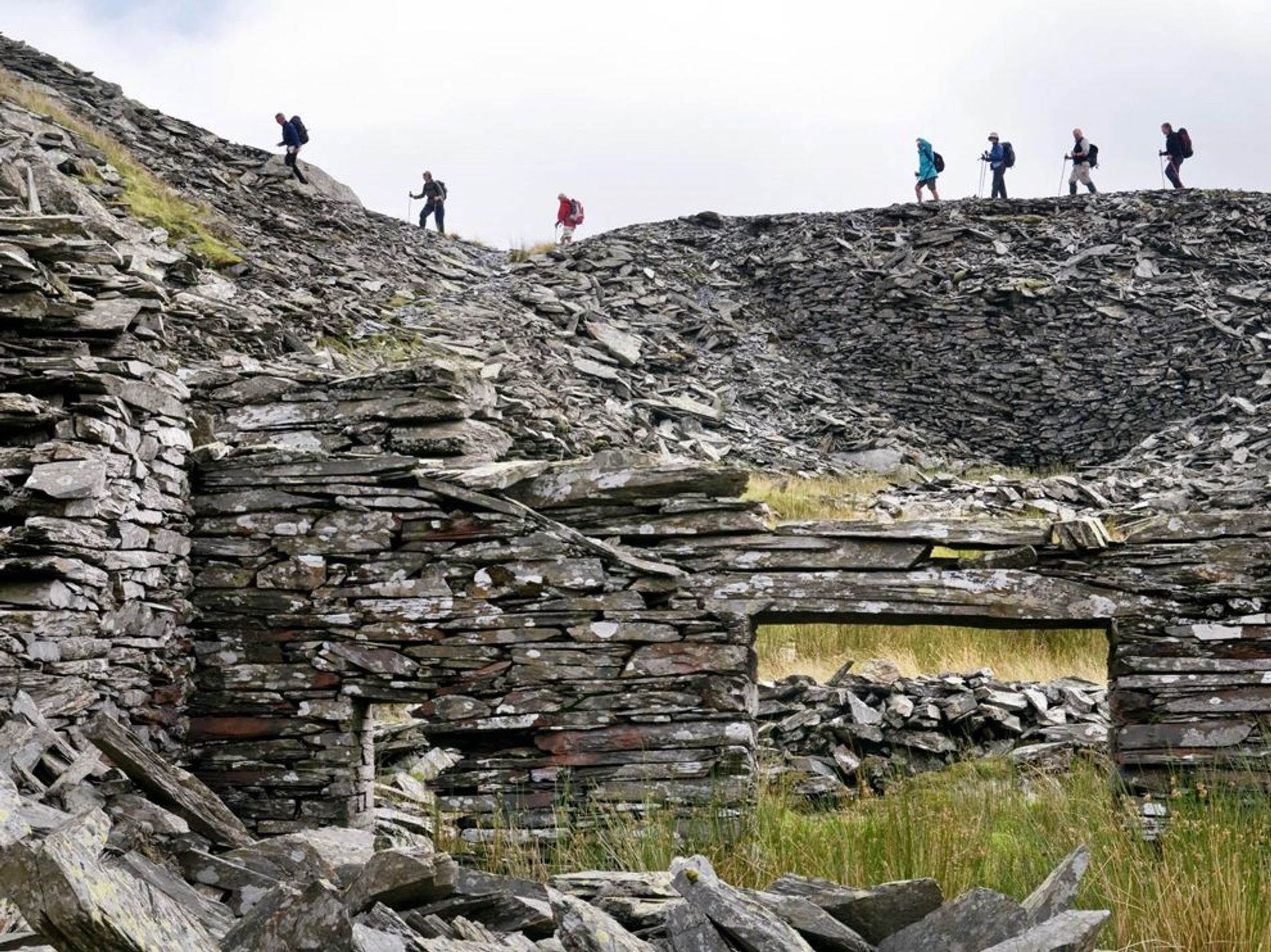 Walkers in Snowdonia National Park pass an abandoned slate quarry.