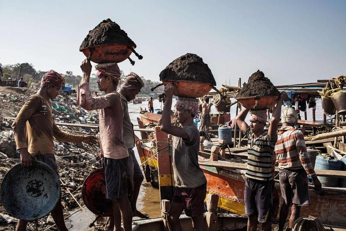 Bangladeshi migrant workers unload sand from Indian-owned boats on the Thane Creek, India.