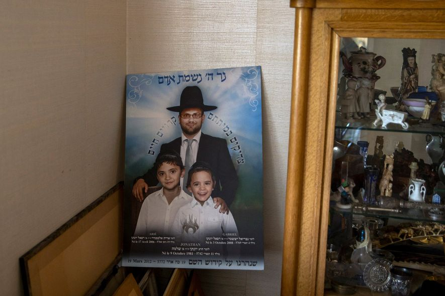A memorial poster of Jonathan and his sons is displayed in Sandler's home in the Paris ...