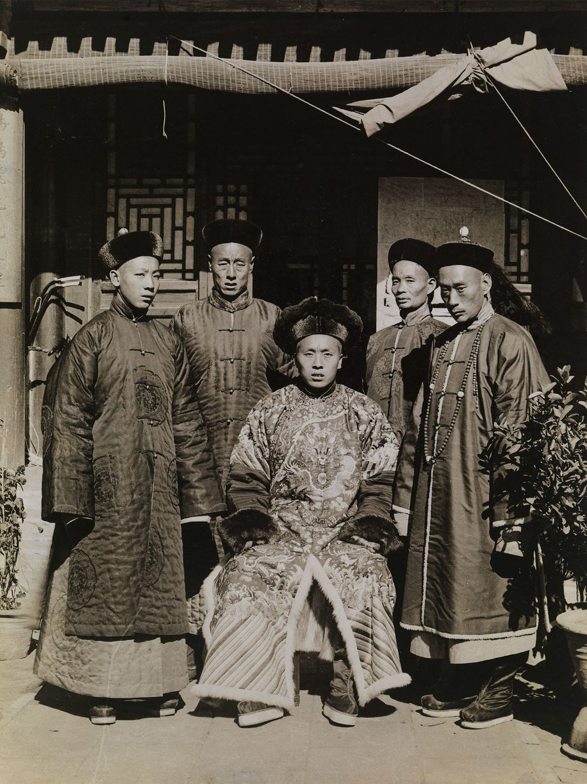 Manchu men in China wear elegant silk clothing and fur hats to show off their social ...