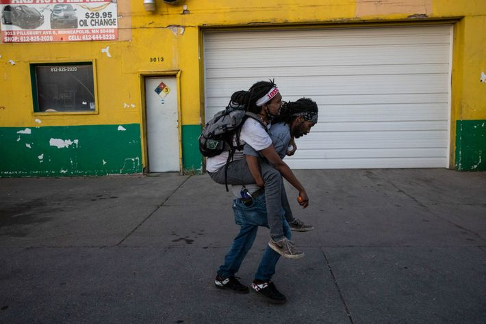 A man carries an injured friend who was hit by police rubber bullets during protests in ...
