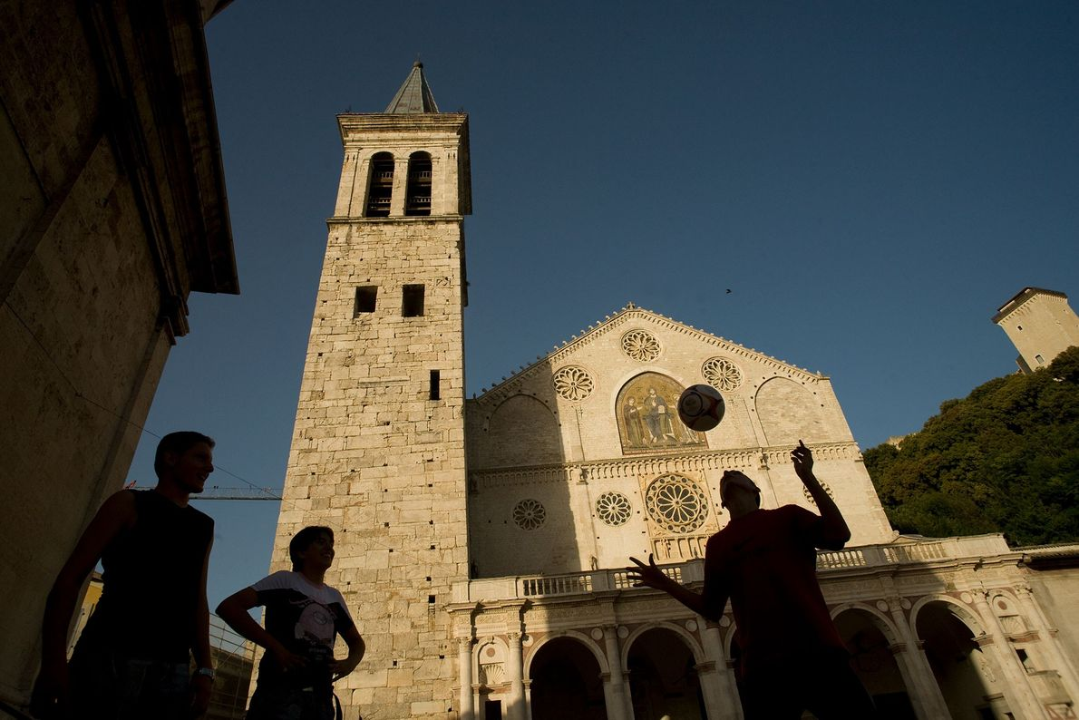 A small group plays football in front of the Cathedral of Santa Maria Assunta in Umbria, ...