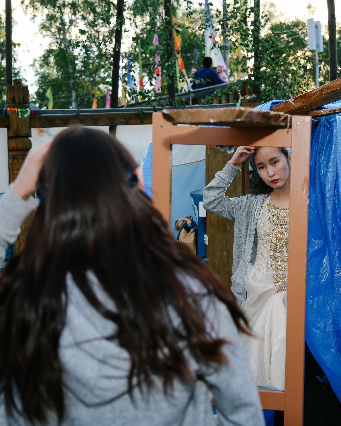A festivalgoer dresses in traditional costume in the village of Amga. Many families spend time together ...