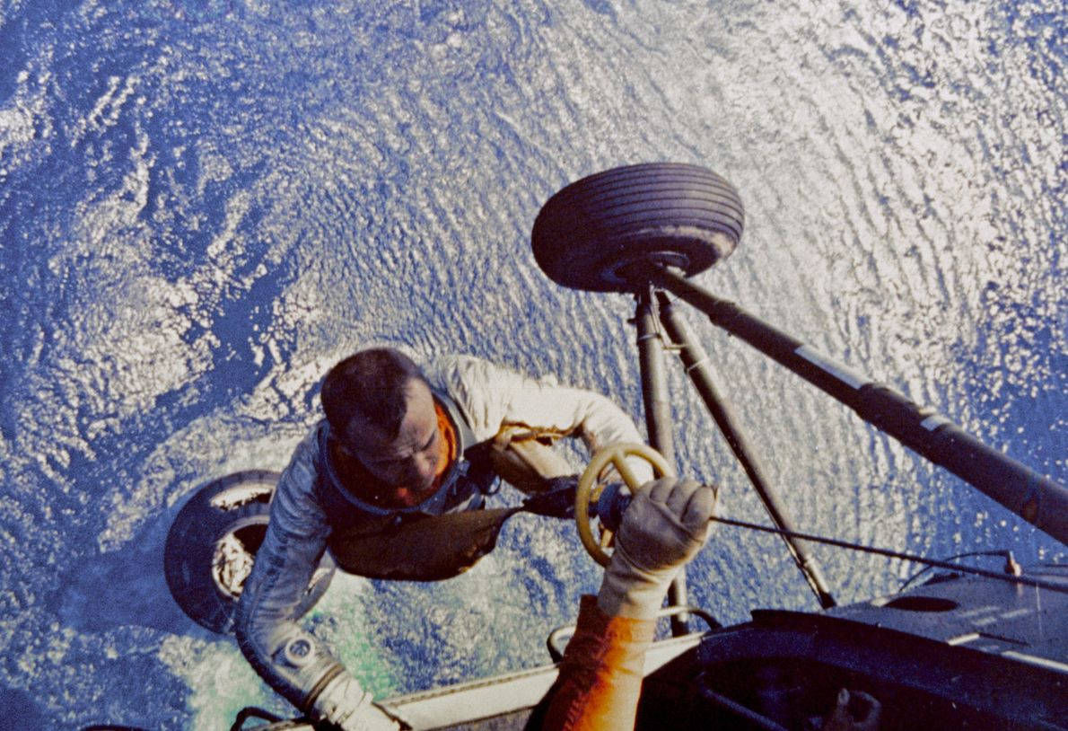 Shepard is pulled aboard a U.S. Marine helicopter after splashdown, May 5th, 1961. Shepard would later ...