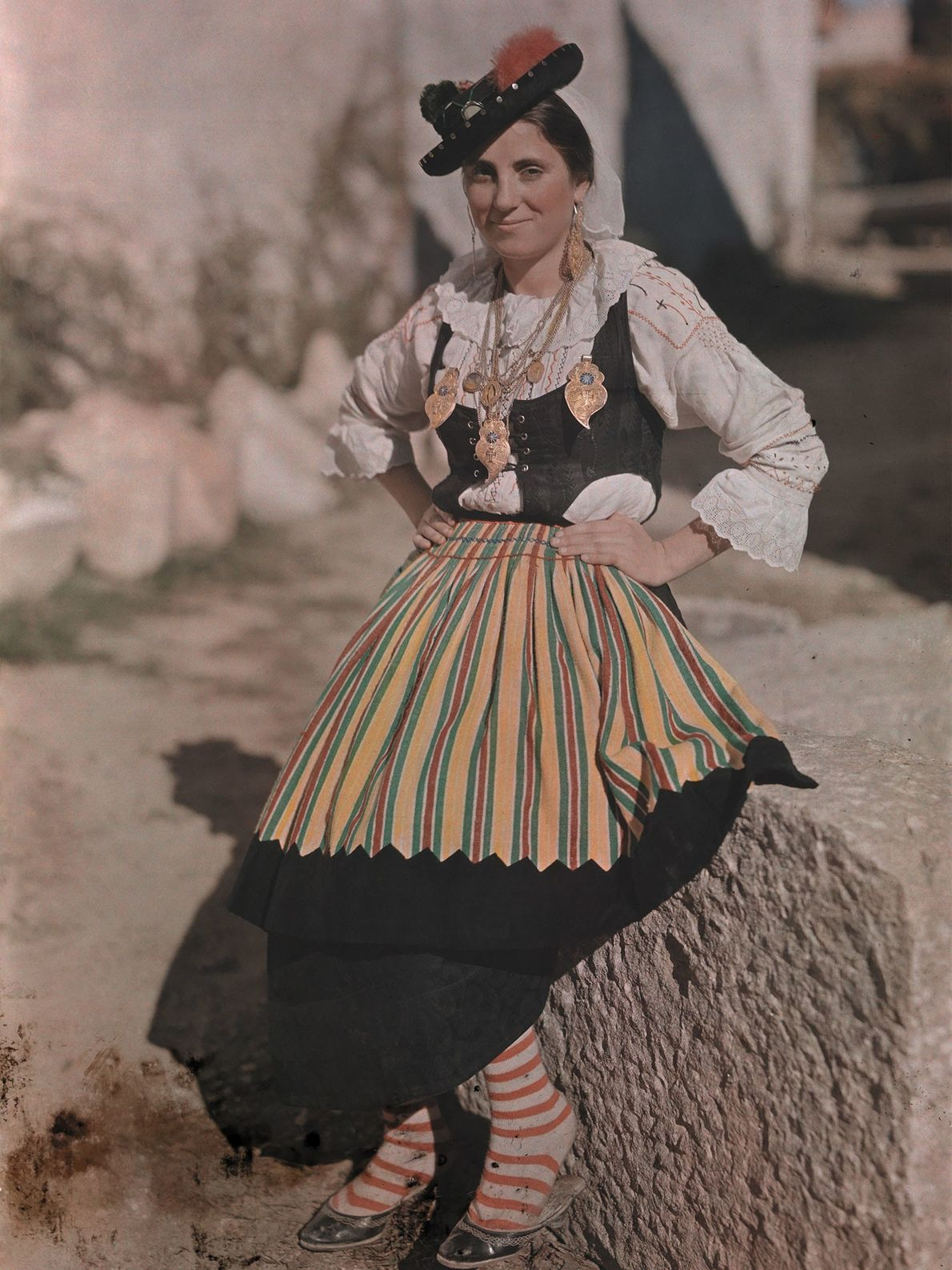 A woman wearing festival attire and a flashy black hat leans on a stone in Braga, ...