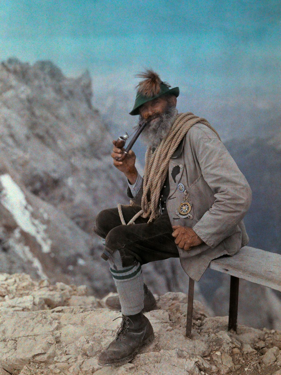 An experienced frontier guide in Zugspitze, Germany, smokes a pipe while wearing his alpine hat, with ...