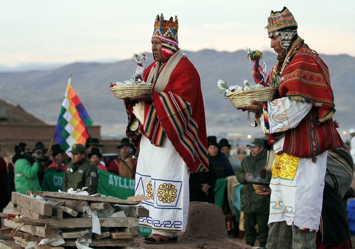 Aymara Indian shamans carry burned, decorated llama fetuses at a sunrise winter solstice ceremony in Tiwanaku, ...