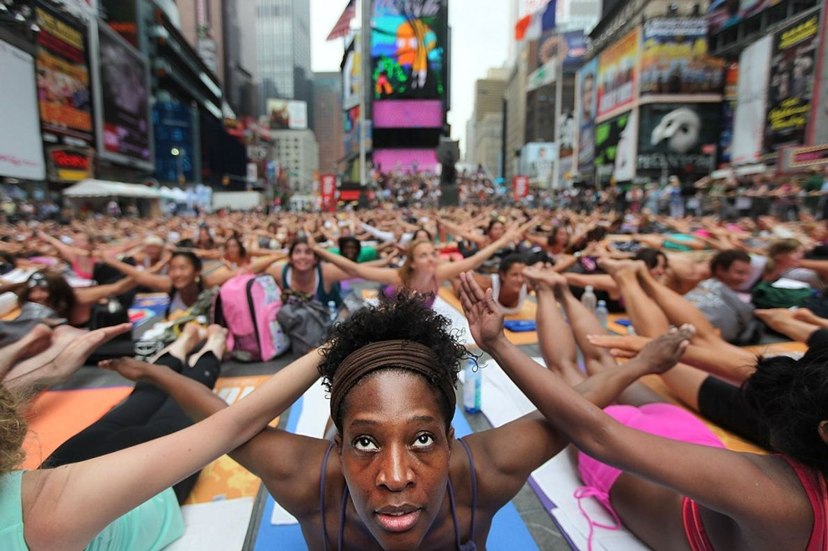 Bernice Acosta and thousands of other yoga enthusiasts crowd car-free Times Square in New York to ...