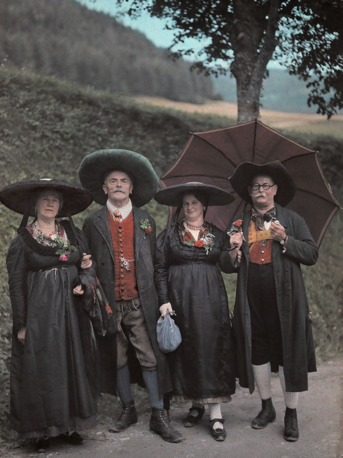 A group of Austrian people wear wide-brimmed hats as they travel down a rural Styrian road ...