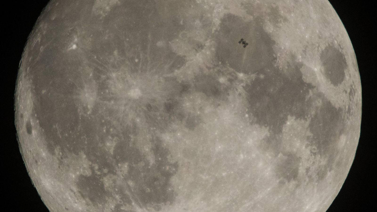 Look carefully and you can see the International Space Station in silhouette as it transits the ...