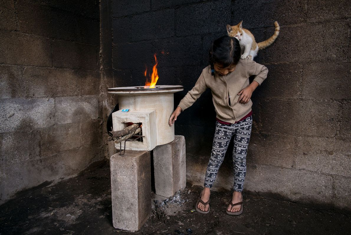 Tania López, seven, plays with her cat in a room in her Guatemala home where walls ...
